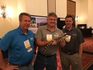 Holding a gator in front of the Ausley Trade Show Booth at Florida Educational Facilities Planners Association FEFPA Summer Conference in Boca Raton